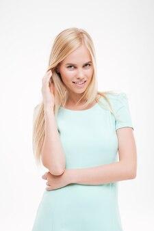 白い壁に孤立した髪を保持し、正面を見ているきれいな女性