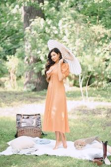 낮에는 자연 속에서 우산을 들고 오렌지 드레스를 찾고 예쁜 아가씨.