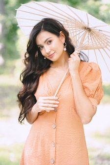Pretty lady holding umbrella and looking in nature in orange dress during daytime .