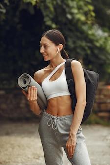 公園のきれいな女性。ブルネットはヨガの準備をします。スポーツスーツの女の子。