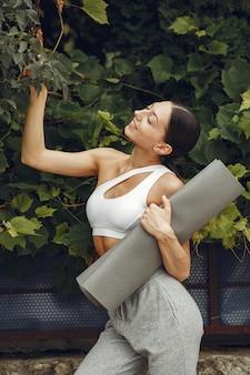 Симпатичная дама в парке. брюнетка готовится к йоге. девушка в спортивном костюме.