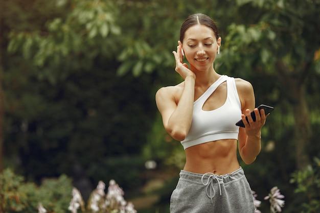 公園のきれいな女性。携帯電話でブルネット。スポーツスーツの女の子。