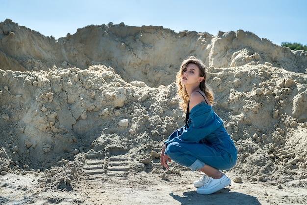 파란색 작업복을 입은 예쁜 아가씨가 모래 채석장을 걷고 있습니다.