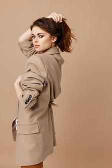 コートを着たきれいな女性は彼女の頭とベージュの背景の髪をまっすぐにします