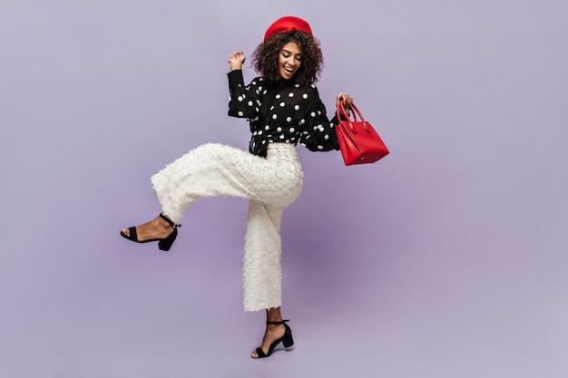 검은색 현대적인 블라우스를 입은 짙은 곱슬머리와 빨간 핸드백을 들고 웃고 포즈를 취하는 넓은 흰색 바지를 입은 좋은 분위기의 예쁜 아가씨
