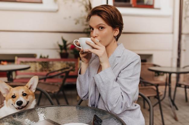 회색 재킷에 예쁜 아가씨는 거리 카페에서 커피를 마신다. 세련된 정장을 입은 젊은 여성이 차를 즐기고 외부 corgi와 함께 포즈를 취합니다.