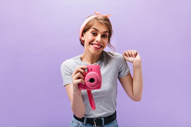 ピンクのカメラでポーズをとる灰色のtシャツのきれいな女性。トレンディな服と孤立した背景に笑みを浮かべてクールなバンダナの魅力的な若い女性。