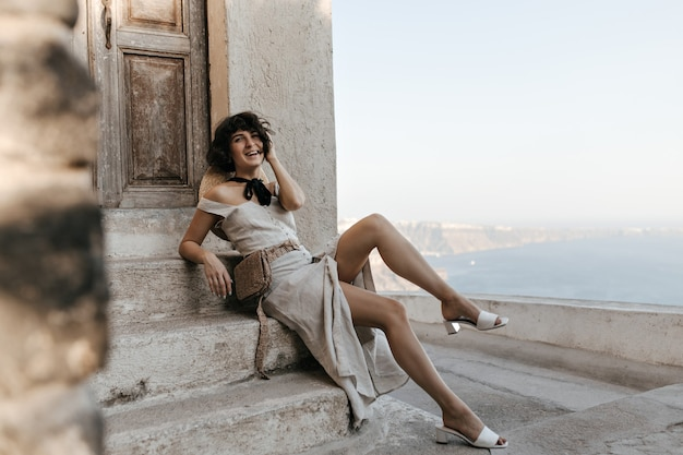 Красивая дама в бежевом платье миди с соломенной сумкой на талии улыбается возле дома с видом на море