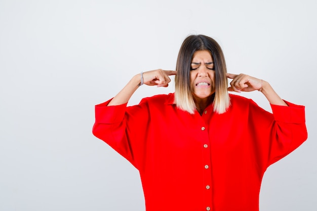 赤いブラウスのきれいな女性が指で耳を塞ぎ、イライラしているように見える、正面図。