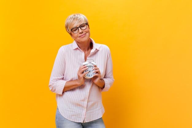 縞模様のシャツと眼鏡のきれいな女性は、孤立した背景に目覚まし時計を保持します