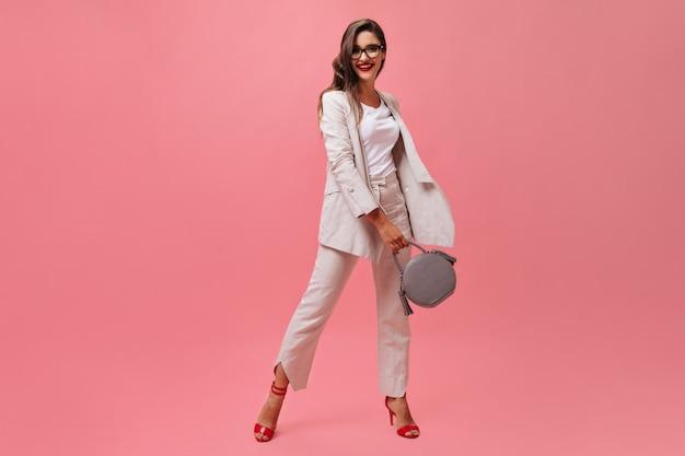 ピンクの背景に灰色のハンドバッグとスーツと眼鏡のきれいな女性のポーズ。明るい服の笑顔で暗いウェーブのかかった髪の素敵な女性。