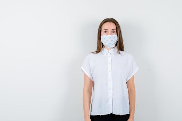 Красивая дама в футболке с маской позирует, стоя и уверенно выглядя