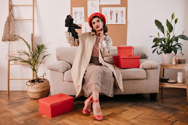トレンチコートを着たきれいな女性が思慮深くポーズをとり、靴を履きます。スタイリッシュな服装のきれいな女性は、赤いハイヒールの居心地の良いソファに座っています。