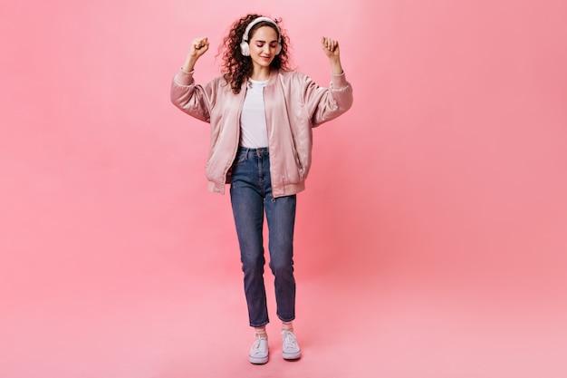 白いヘッドフォンのきれいな女性はピンクの背景で踊る