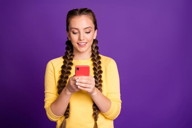 Красивая дама с длинными косами держится за телефонные руки, читая новые положительные комментарии, носить повседневный желтый пуловер, красные брюки, изолированные на стене фиолетового цвета