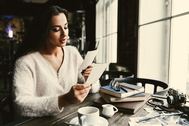 Довольно леди смотрит на старые фотографии, сидя за столом в кафе