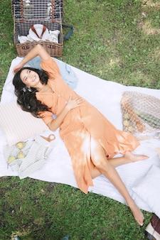 Signora graziosa che si trova e che sorride in vestito arancio in natura durante il giorno.