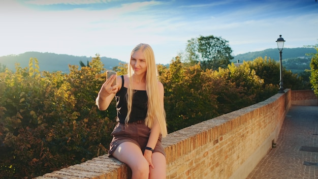 Pretty lady making selfie on smartphone in front of beautiful nature landscape