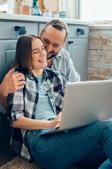 노트북과 그녀의 사랑하는 남자 친구가 그녀의 어깨를 껴안고 앉아 부엌 바닥에 예쁜 아가씨