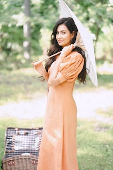 Pretty lady in orange dress holding umbrella and looking in nature during daytime .