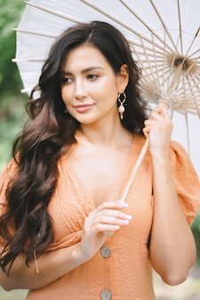 Pretty lady in orange dress holding umbrella and thinking in nature during daytime .