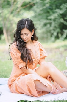 Pretty lady in orange dress sitting and looking below in nature during daytime .
