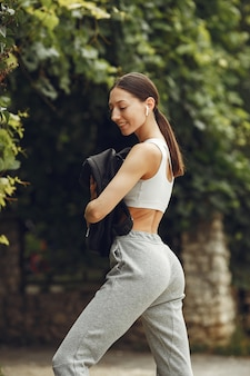 Pretty lady in a park. brunette prepare to yoga. girl in a sportsuit.