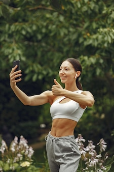 Pretty lady in a park. brunette with mobile phone. girl in a sportsuit.