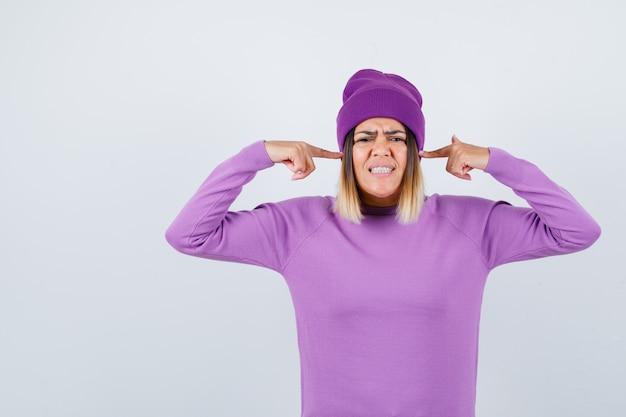 きれいな女性がセーター、ビーニーに指で耳を差し込んで、イライラしているように見える、正面図。