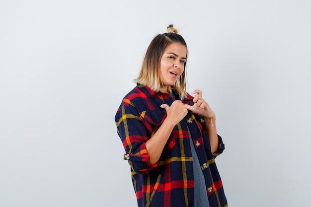 Bella signora che indica se stessa con i pollici in camicia casual e sembra orgogliosa. vista frontale.