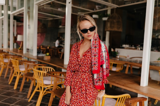 Красивая дама позирует в летнем кафе в ярком летнем платье, солнцезащитных очках и аксессуарах