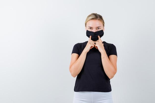 예쁜 아가씨 검은 티셔츠에 손가락으로 마스크를 누르면, 검은 마스크 절연