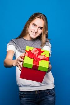 예쁜 아가씨는 당신에게 밝은 giftbox를 열 것을 제안합니다