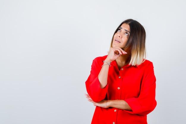 Bella signora che puntella il mento a portata di mano, alza lo sguardo in camicetta rossa e sembra pensierosa. vista frontale.