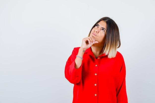 Bella signora che puntella il mento a portata di mano, alzando lo sguardo in camicetta rossa e guardando premurosa, vista frontale.