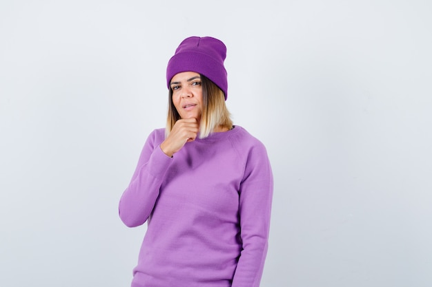 セーター、ビーニーで手に顎を支え、賢明に見えるきれいな女性。正面図。