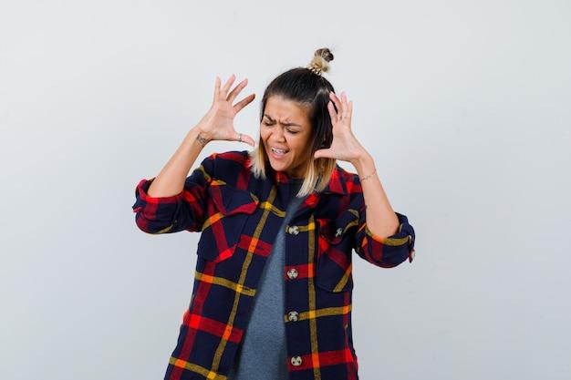 カジュアルなシャツを着て頭の近くで手を上げて激怒しているきれいな女性。正面図。