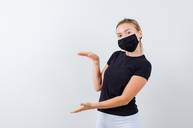 Bella signora che mostra un cartello di grandi dimensioni in maglietta nera, maschera nera isolata