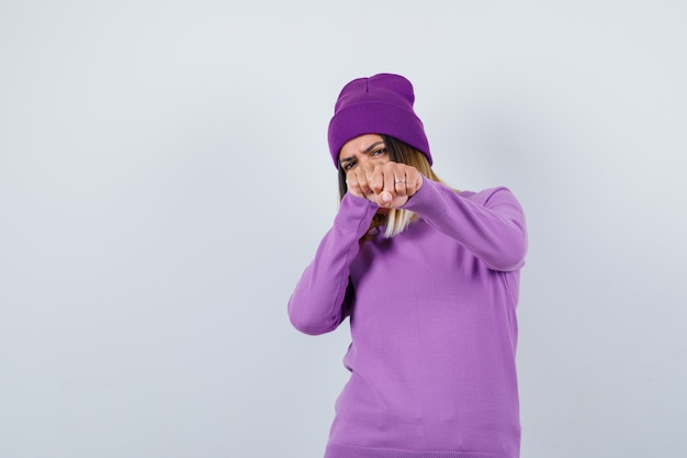 Bella signora in piedi in posa di combattimento in maglione, berretto e dall'aspetto fiducioso. vista frontale.
