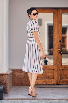 Pretty lady in striped dress approaching the door