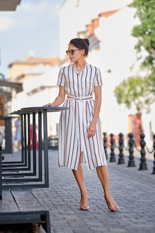 Pretty lady in striped dress in the city in sunny day