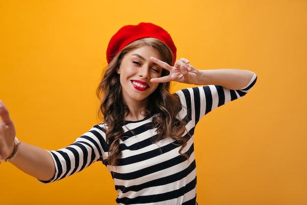 Bella signora sulla camicia a righe mostra il segno di pace e fa selfie. donna felice con rossetto rosso in bei vestiti e berretto luminoso in posa.