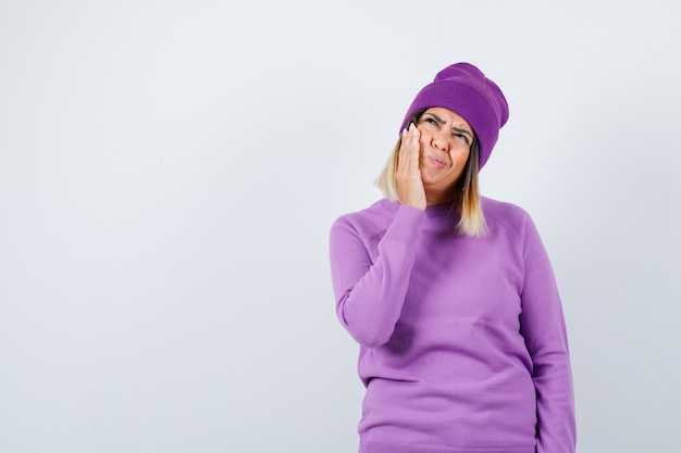 Pretty lady suffering from toothache, looking up in sweater, beanie and looking uncomfortable , front view.