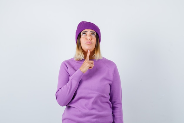 Pretty lady in sweater, beanie holding finger under chin, looking up and looking dismal , front view.