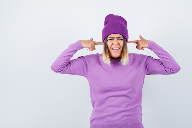 Pretty lady in sweater, beanie making suicide gesture and looking mournful , front view.