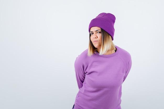 Bella signora in maglione, berretto con le mani dietro la schiena e dall'aspetto curioso, vista frontale.