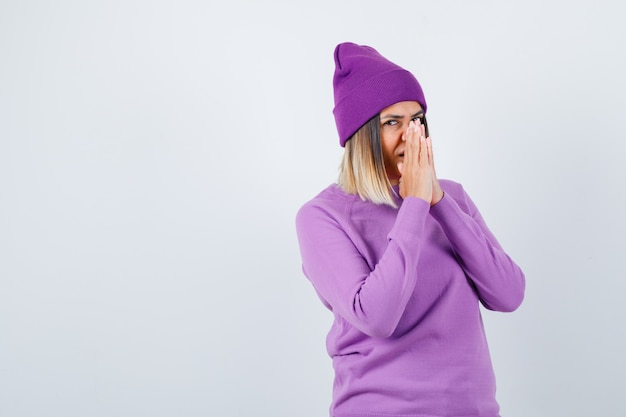 Pretty lady in sweater, beanie with hands in praying gesture and looking dreamy , front view.