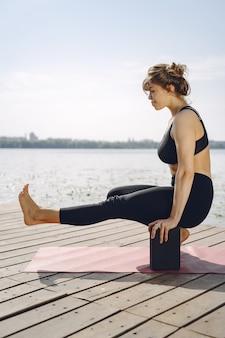 Красивая дама тренируется в летнем парке. брюнетка занимается йогой. девушка в спортивном костюме.