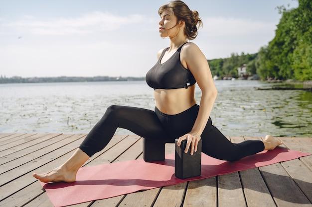 かなりの女性が夏の公園でトレーニング。ヨガをやっているブルネット。スポーツスーツの女の子。