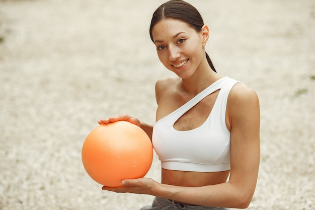 かなりの女性が夏のビーチでトレーニング。ヨガをやっているブルネット。スポーツスーツの女の子。